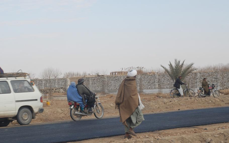 Women in Marjah are covered head to toe in burqas, and seen only in cars or on the backs of motorbikes, here traveling on the town's first paved road.