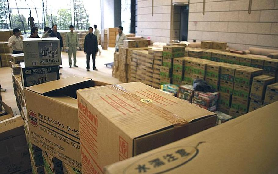 Workers prepare to load an inbound cargo truck with supplies bound for evacuation sites throughout the area at the Sendai Prefectural Headquarters  Building, in Sendai City.