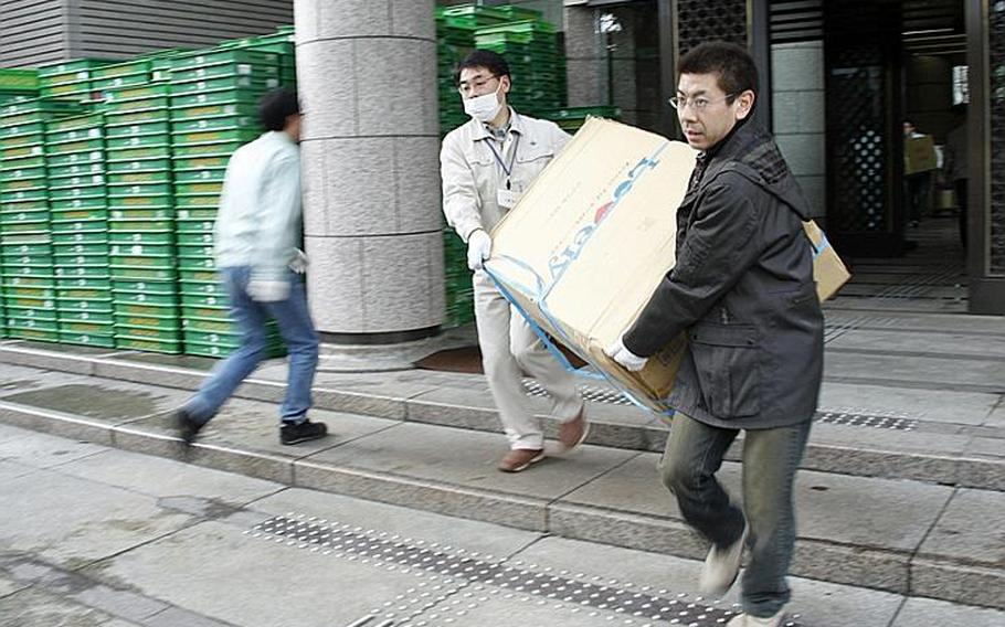 Workers hurry to load cargo trucks with supplies bound for evacuation sites throughout the area at the Sendai Prefectural Headquarters  Building, in Sendai City.