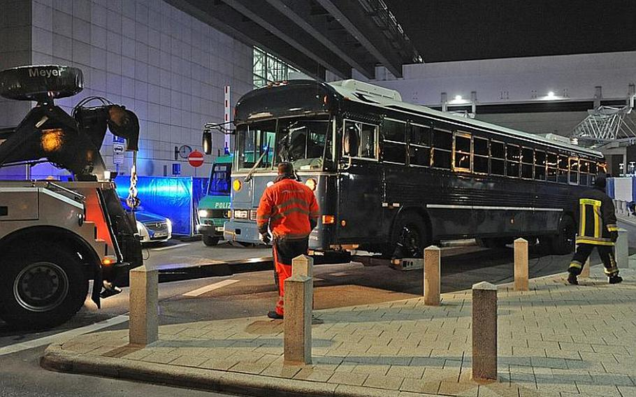 A blue U.S.Air Force bus is towed from Frankfurt airport's Terminal 2 after a shooting that killed two airmen on March 2.