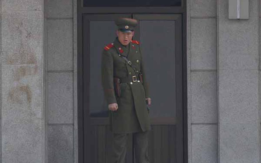 A North Korean soldier peers across the Joint Security Area of the Demilitarized Zone Wednesday as a tour group is led around south of the Military Demarcation Line. An estimated 150,000 people visit the South Korean side of the DMZ every year.