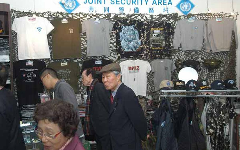 Tourists file Wednesday through the gift shop at the Joint Security Area Visitor Center at Korea's Demilitarized Zone. The most popular items sold there are T-shirts, a plaque featuring a piece of DMZ wire fence and liquor bottled at the Kaesong Industrial Complex in North Korea.