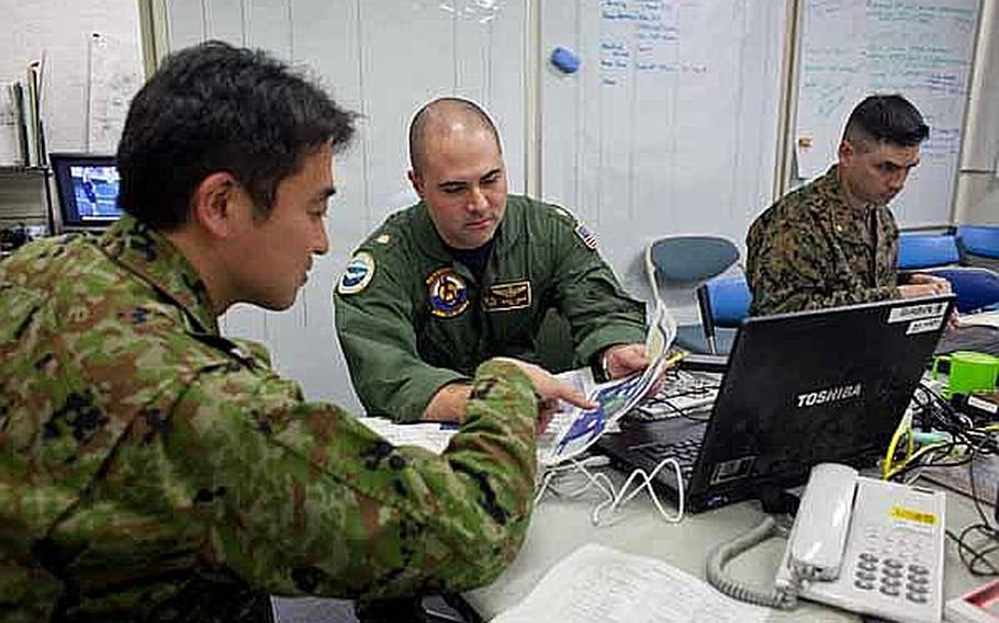 Lt. Cmdr. Barnet Harris, center, assigned to the Bilateral Crisis Action Team at Camp Sendai, Japan, works with Japan Self Defense Force troops to coordinate joint U.S. and Japanese relief efforts.