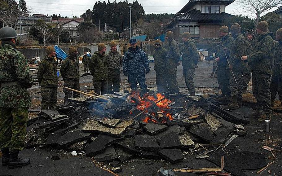 Rear Adm. Jeffrey S. Jones speaks with members of the 31st Marine Expeditionary Unit about ongoing disaster relief efforts on Oshima Island, Japan, on April 4. Sailors with the USS Essex and Marines embarked on the ship finished their work on the island on April 7.