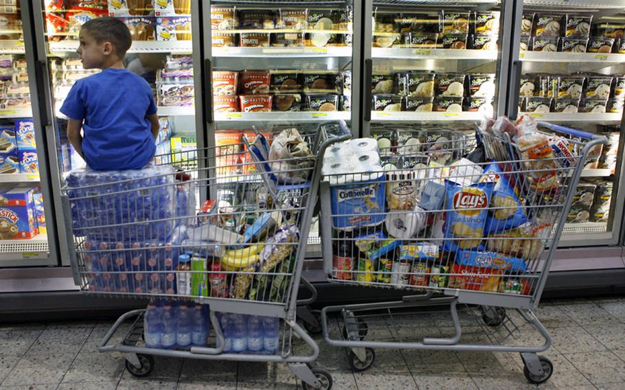 Carson Maxwell sits on the extra water and groceries his mother, Air Force Mst. Sgt. Cynthia Maxwell, was purchasing at Ramstein Air Force Base commissary in Germany on Friday, April 8, 2011. People were out in force on Friday stocking up in case the commissaries close due to the government shutdown.