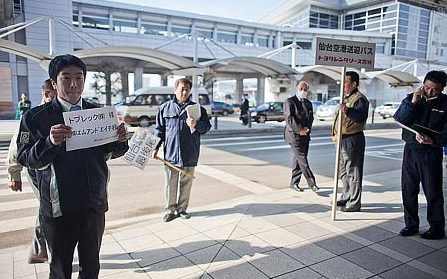 Transportation providers hold signs outside the terminal of Sendai Airport after a Japan Airlines Express flight from Haneda Airport landed - making it the first commercial flight to the airport since the March 11 tsunami ravaged the airport and region.