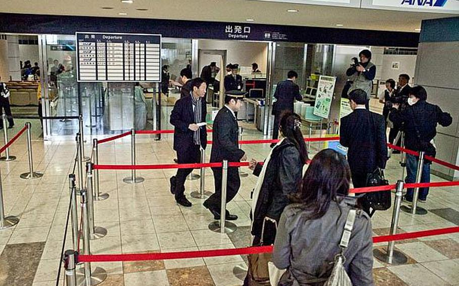 People begin to go through security in preparation to board the first flight to depart Sendai Airport in Sendai, Japan, since the March 11 tsunami ravaged the airport and region.
