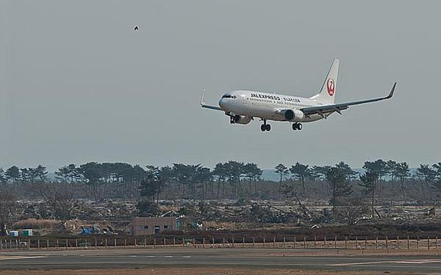 A Japan Airlines Express flight from Haneda Airport lands at Sendai Airport in Sendai, Japan, making it the first commercial flight to the airport since the March 11 tsunami ravaged the airport and region. The message, 'Let's get through this, Japan' was written on the side of the Boeing 737.