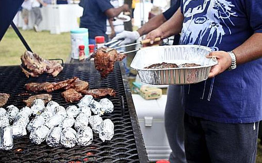 Yokota Air Base resident Christopher Black tends to a grill Saturday at 'Tomodachi Stock' at the Sakura Shell on base, the site of a free concert to raise money through concessions and Red Cross donations for the tsunami victims in northern Japan.