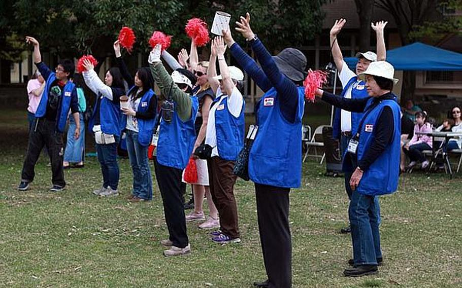 Volunteers from the American Red Cross cheer for donations at 'Tomodachi Stock'  Saturday at the Sakura Shell on Yokota Air Base, site of a free concert to raise money for the tsunami victims in northern Japan.