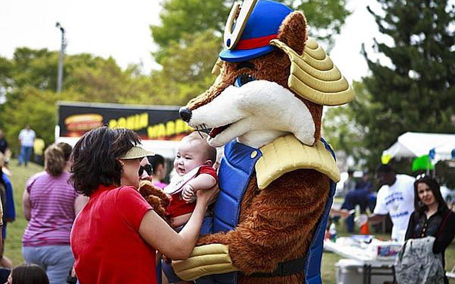 The 374th Force Support Squadron's mascot, 'Samurai Fox,' greets a young concert attendee of 'Tomodachi Stock' Saturday at the Sakura Shell on Yokota Air Base, the site of a free concert to raise money through concessions and Red Cross donations for the tsunami victims in northern Japan.