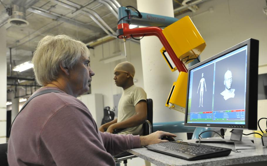 Brian Corner, a scientist at the Natick Soldier Research, Development and Engineering Center in Massachusetts, measures a soldier's head and face using a 3-D scanner.