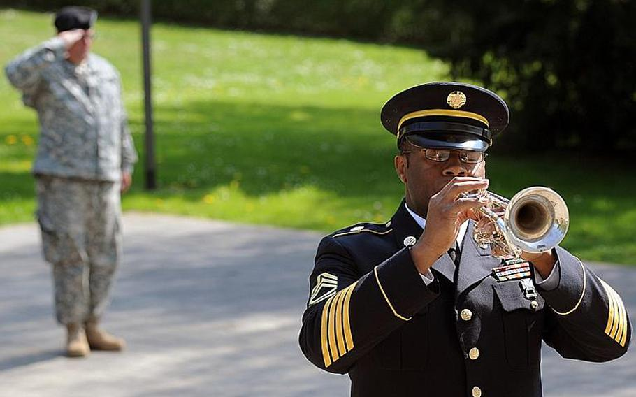 Staff Sgt. Joel Trammel salutes as Sgt. 1st Class Brandon Madison of the U.S. Army Europe Band plays taps at the conclusion of the memorial ceremony Wednesday for Staff Sgt. Jose M. Caraballo Pietri, in Baumholder, Germany.