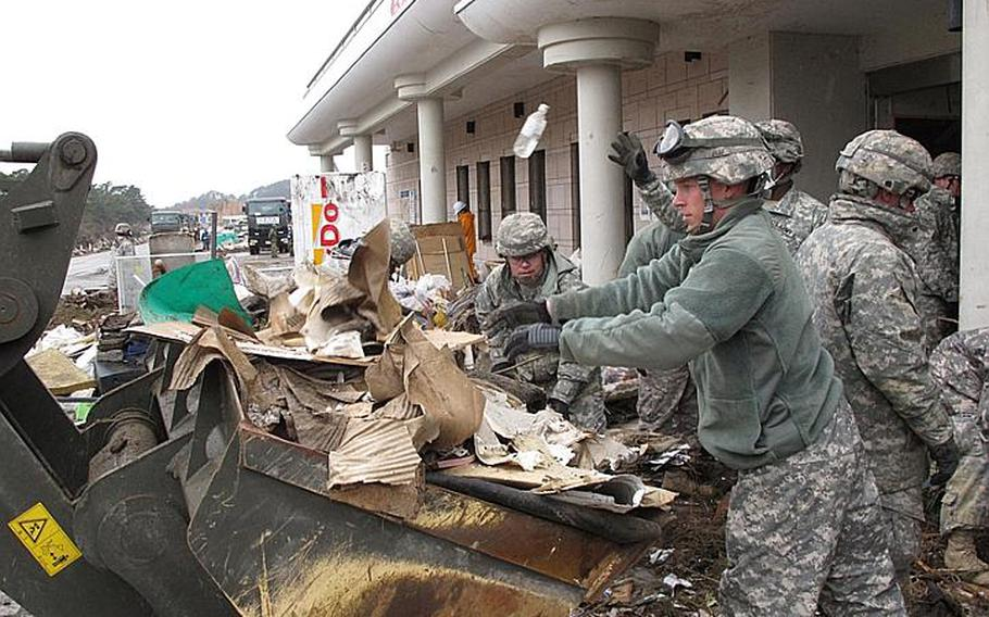 Spc. Timothy Jones, right, and Spc. Ivan Santos, background center, toss debris while clearing out Nobiru train station, in Japan's tsunami-battered northeast, in April 2011.