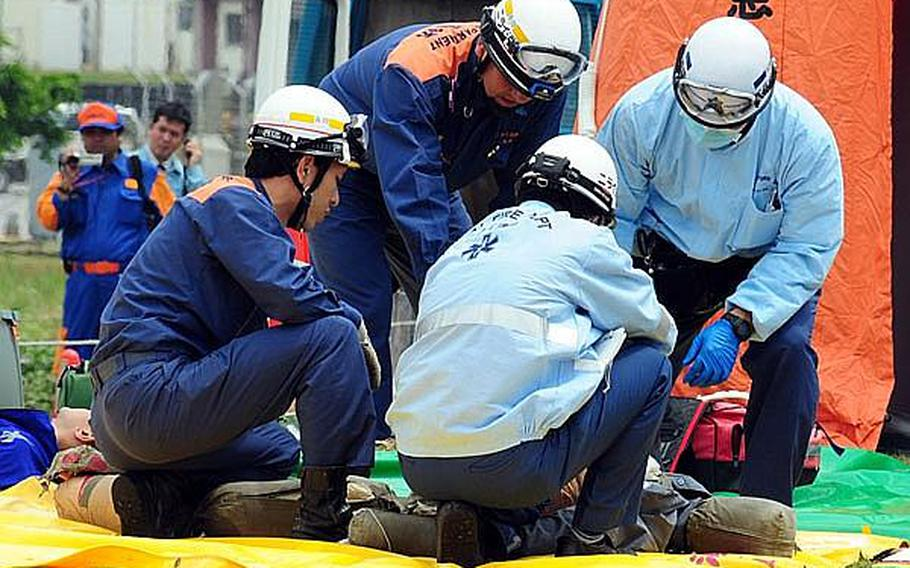 Japanese emergency responders tend a simulated casualty during a bilateral training exercise between the U.S. military and Japanese emergency response organizations. Approximatey 180 people participated in the annual exercise which is designed to test and strengthen U.S. and Japanese understanding and cooperation in real world scenarios.