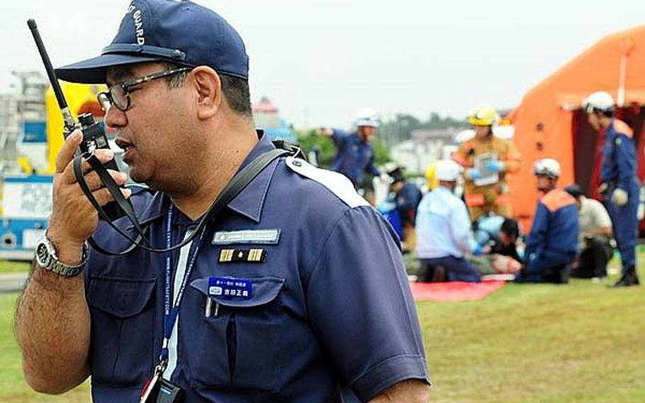 A Japanese coast guard member relays information to members of his response team. Many different elements of Japanese emergency response teams participated in this year?s bilateral training exercise which involved a simulated aircraft crash into an urban area after the pilots ejected into the ocean.