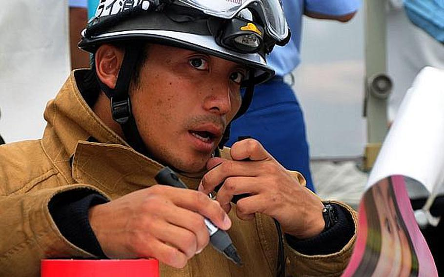 A Japanese emergency response team member relays information from a temporary command center to members of his team.  Many different elements of Japanese emergency response teams participated in this year?s bilateral training exercise, which involved approximately 120 Japanese and 60 U.S. servicemembers.