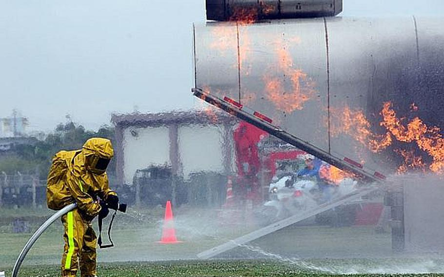 A firefighter readies his hose in preparation for dousing a simulated helicopter fire  during an annual bilateral training exercise between the U.S. military and Japanese Emergency Response Teams. This is the sixth year of the exercise with each year getting more elaborate as more elements are added.