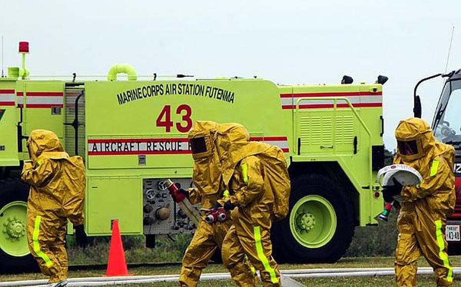 Firefighters grab hoses in preparation for dousing the flames on a simulated aircraft crash. The scenario was enacted as part of an annual bilateral training exercise between Japanese Emergency Response Teams and all branches of the U.S. military.