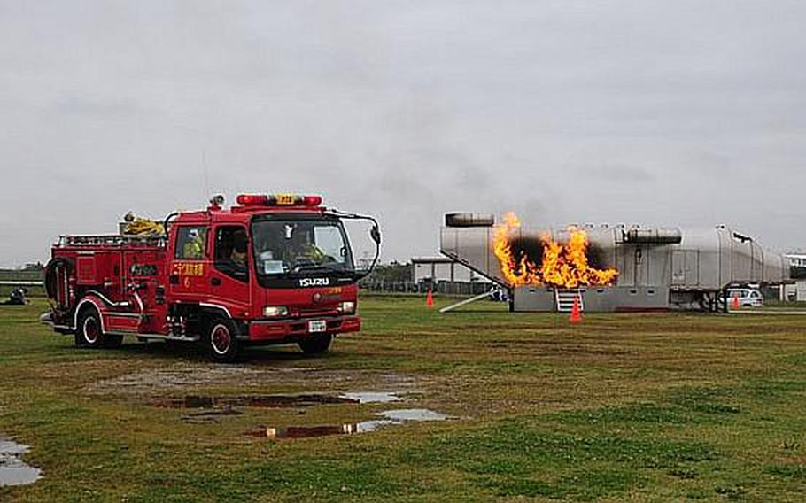 A Japanese fire truck pulls up alongside a simulated aircraft crash during Wednesday's annual bilateral training exercise between Japanese Emergency Response Teams and the U.S. military. This is the sixth year of the exercise, which is designed to improve and reinforce emergency response procedures.