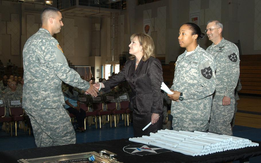 University of Maryland University College President Susan Aldridge, center, congratulates one of more than 200 Warrior University students honored at a recognition event Thursday at Camp Casey in South Korea. The program encourages soldiers to take college classes, and has been cited by Maj. Gen. Michael Tucker, at right behind Aldridge, as a reason crime is down significantly in his 2nd Infantry Division.