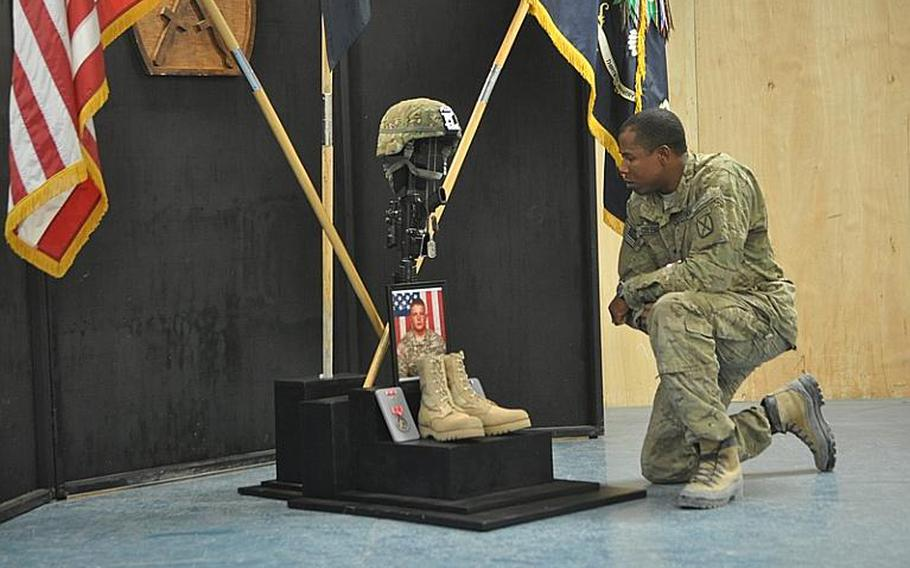 Spc. Henry Coleman remembers Spc. Richard Emmons III, who was killed by a rocket-propelled grenade earlier this week, at a tribute service on Thursday at Forward Operating Base Altimur in Logar province. A shrine in Emmons' honor included a framed photo, his helmet, rifle and boots and the Bronze Star and Purple Heart he received posthumously.