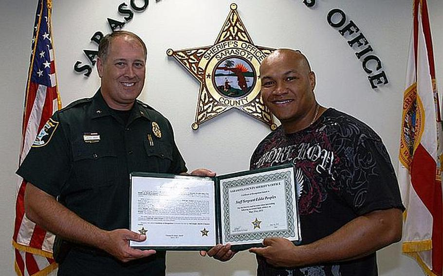 Sheriff Tom Knight,left, presents a Certificate of Recognition to Army Staff Sergeant Eddie Peoples for disarming and subduing the man who robbed a Bank of America, in Sarasota, FL, on Tuesday. Courtesy Sarasota County Sheriff's Office