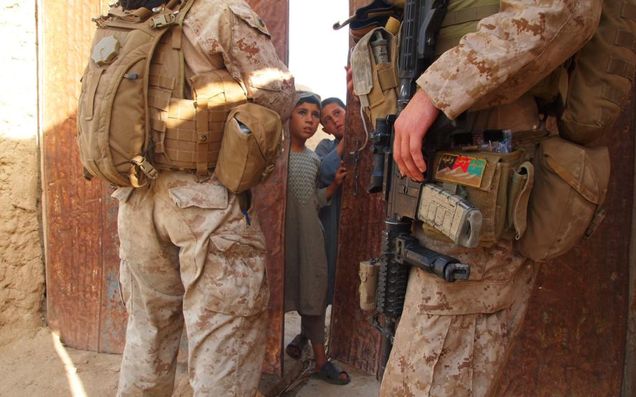 Marine Sgt. Randy Williamson, right, a squad leader from Stroudsburg, Pa., and an interpreter talk to some young boys early in the morning on May 27 while trying to find an English-speaking shopkeeper they know lives in the area. Williamson is the leader of 1st Squad, 3rd Platoon, Company I, 3rd Battalion, 2nd Marine Regiment.