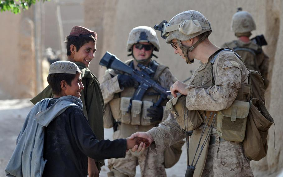 Lance Cpl. Jeremy Reckner, a squad automatic weapon gunner with Company I, 3rd Battalion, 2nd Marines, shakes hands with a local boy while on patrol in a village a few miles north of the Musa Qala district center.