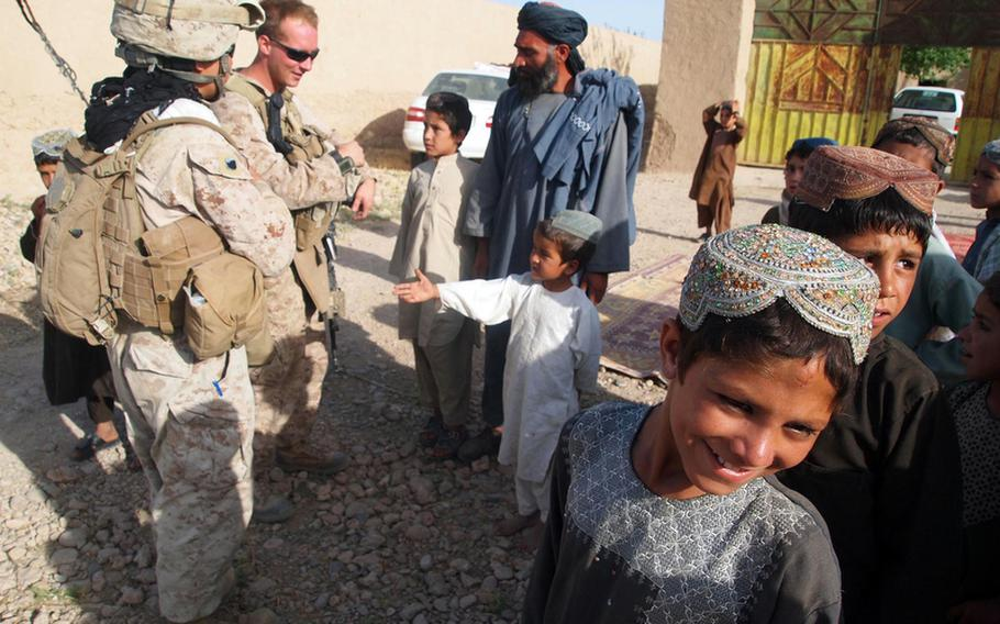 A small boy extends his hand to Marine Sgt. Randy Williamson, a team leader from Stroudsburg, Pa., as he chats with a groom before his wedding in a small village north of Musa Qala's district center. The Marines conduct regular patrols to deter Taliban activity, to give a sense of security to the locals, and to build the population's trust in the Marines, who are engaged in a fierce contest with insurgents for the hearts and minds of the people.