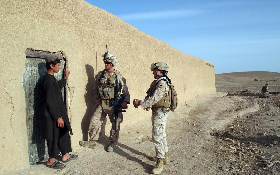 Marine Sgt. Randy Williamson and an interpreter speak with the son of a local mullah with whom the Marines have forged a relationship. The mullah, however, was out for the morning, and the Marines continued their early morning patrol in search of other locals to talk with.