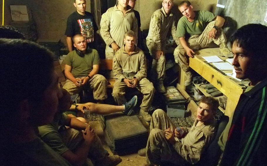 Marine team leader Sgt. Randy Williamson, sitting on the table at right, listens along with his troops May 26 as his words are translated to Afghan soldiers who will accompany them on a patrol early the next morning.