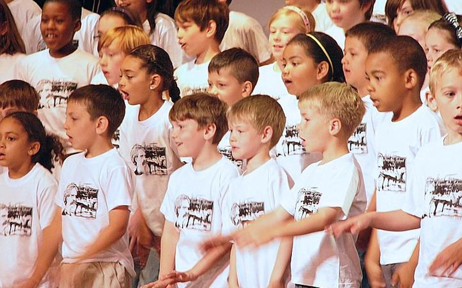 Wearing commemorative T-shirts, the school's pupils sing their farewell to Mark Twain Elementary School in Heidelberg, Germany, on Friday. The school is closing later this month after 59 years.