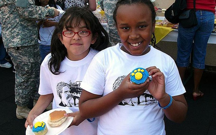 Fourth-graders Seville Kress, left, and and Da?Zha Loney share memories and cupcakes Friday at the picnic that followed the closing ceremony for Mark Twain  Elementary School in Heidelberg, Germany.