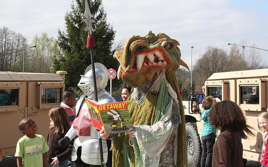 Nancy Hammack, Vilseck Elementary School principal, dressed as a dragon and Becky Balcer, assistant principal, dressed as a knight in the front of Vilseck Elementary school following the students successful completion of Red Hot Reader Month. Courtesy of Vilseck Elementary School