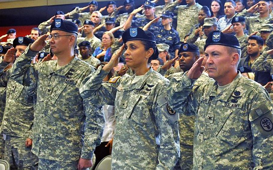 """Army Col. John M. Cho, left,  Army Brig. Gen. Nadja Y. West, center, and Army Col. Jeff B. Clark, right, salute during the playing of """"The Star Spangled Banner."""" After the national anthem, all three took part in a change of command ceremony, in which Cho handed command of Landstuhl Regional Medical Center to  Clark.   Seth Robbins/Stars and Stripes"""