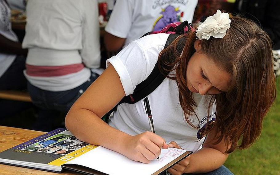 Mannheim High School senior Krystal Hartke writes in a schoolmate's yearbook following a closing ceremony for the high school and middle school on Thursday.