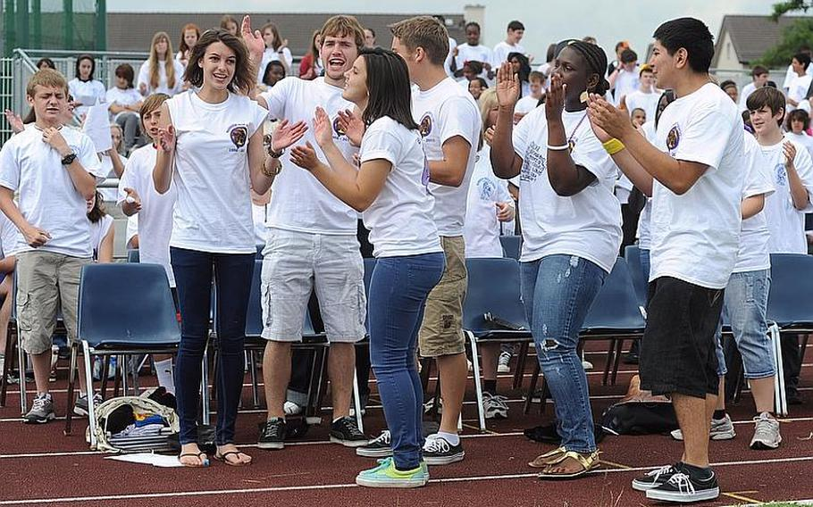 """Members of the Mannheim High School drama club dance and sing """"Time of My Life"""" at the """"Moving On"""" celebration on Woods Memorial Field on Thursday. The ceremony marked the closing of Mannheim High after 55 years and the closing of the middle school after 36 years. In the background are middle school students."""