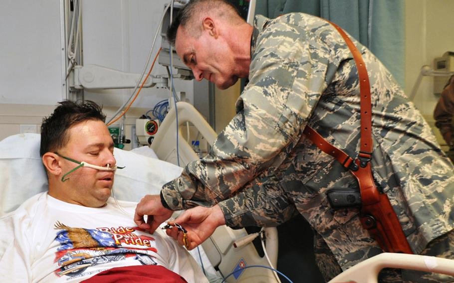 Brig. Gen. Darryl Roberson, 455th Air Expeditionary Wing commander, pins a Purple Heart Medal on Tech. Sgt. James Davis, of the 83rd Expeditionary Rescue Squadron, on April 23, 2011, the same day Davis was wounded while on a recovery mission in Afghanistan.