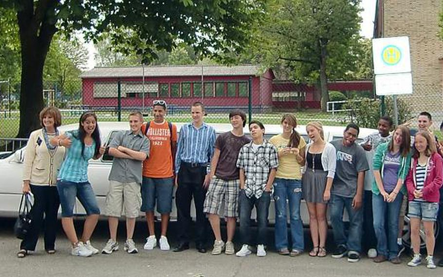 Susan Krummrei stands in front of a limousine with 18 students from her final class before the group gets ready to depart Wiesbaden High School en route to lunch at Vapiano in downtown Wiesbaden.