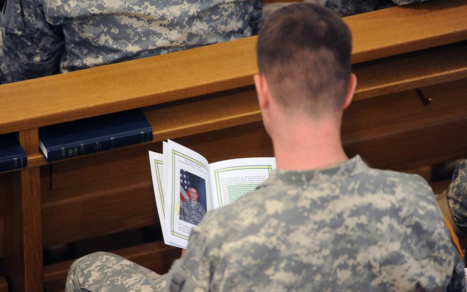 A soldier reads about Spc. Tyler Kreinz's military career during the memorial ceremony Wednesday for Kreinz,  Sgt. 1st Class Alvin Boatwright, Staff Sgt. Edward Dixon and Staff Sgt. Alan Snyder in Baumholder, Germany. The four 170th Brigade Combat Team soldiers were killed in Afghanistan when their vehicle overturned on June 18.