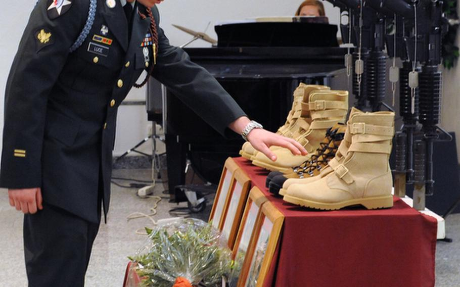 Spc. Steven F. Luce pays his final respects to Sgt. 1st Class Alvin Boatwright, Staff Sgt. Edward Dixon, Staff Sgt. Alan Snyder and Spc. Tyler Kreinz, following a memorial ceremony Wednesday in Baumholder, Germany. The four 170th Brigade Combat Team soldiers were killed in Afghanistan when their vehicle overturned on June 18.