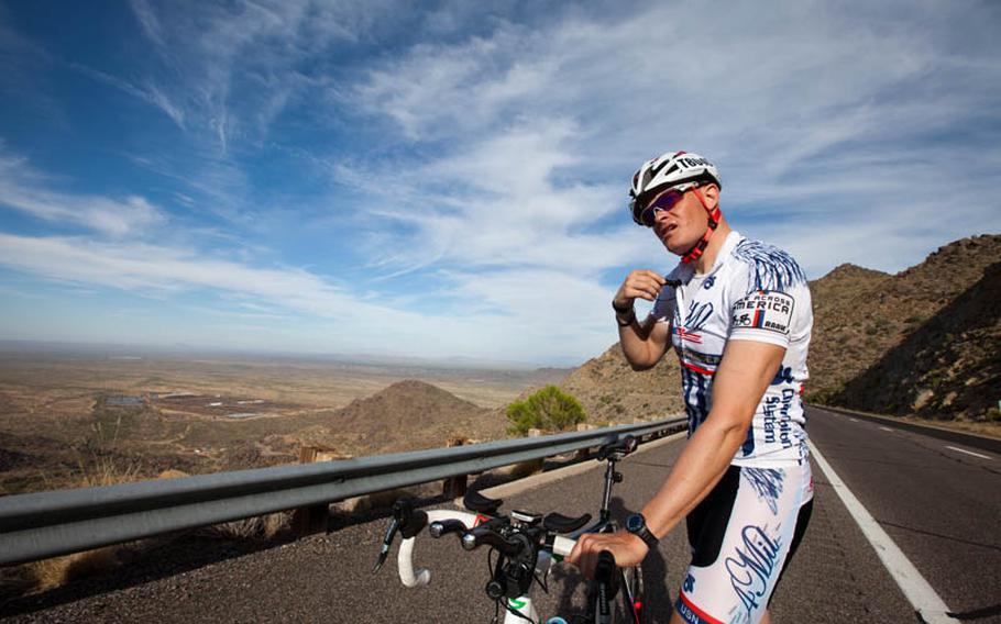 Kyle Pitman checks his race radio before starting a climb in the Arizona desert.