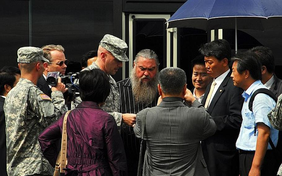 Steve House, center, studies a map of Camp Carroll's helipad area and discusses where he believes he buried barrels of Agent Orange in 1978. Surrounding him are South Korean lawmakers and members of a joint U.S.-South Korean task force who are investigating his claims. Standing beside House is Col. Joseph Birchmeier, a U.S. Forces Korea engineer.
