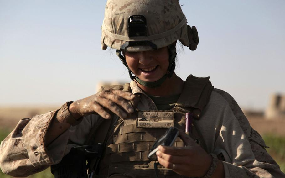 Marine Lance Cpl. Aurora Talarico, a 24-year-old Female Engagement Team member from Chicago, cleans mud off her camera after falling in a flooded cornfield during a patrol July 23. Half the Marines on the patrol and one Afghan fell in the mud. Talarico took the mess in stride, but the Afghan refused to go on.