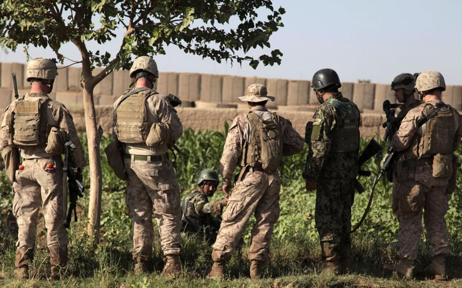 U.S. Marines of Company A, 1st Battalion, 3rd Marine Regiment.try to convince an Afghan soldier, sitting on the edge of an irrigation ditch, to continue patrolling after he fell in the mud about 50 yards from the gate of Patrol Base Amir. The  soldier refused to go on.