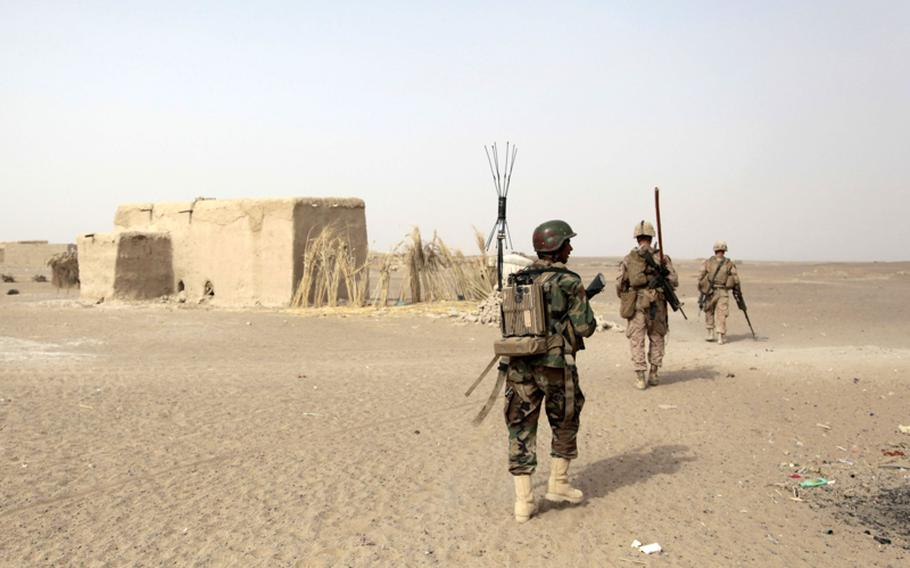 An Afghan National Army soldier carries on his back a device to keep remote-controlled bombs from exploding. The soldier volunteered to carry the device, relieving a Marine of the heavy piece of equipment for the return-leg of a patrol.
