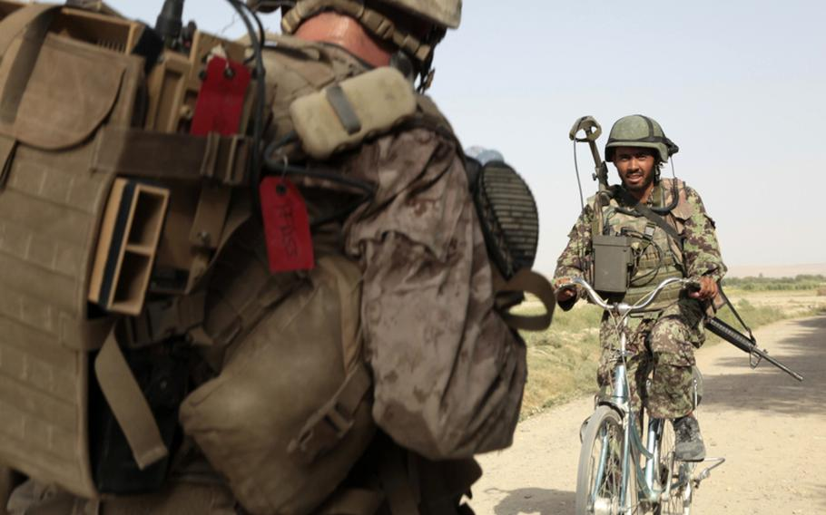 Rahmazan, an Afghan soldier, rides a bicycle he borrowed from an Afghan boy during a joint patrol with U.S. Marines on July 21. The Marines of Company B, 1st Battalion, 3rd Marine Regiment think Rahmazan looks like British actor and comedian Russell Brand.