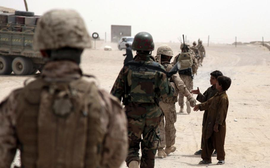 A Marine of Company C, 1st Battalion, 3rd Marine Regiment, shakes hands with an Afghan boy during a patrol July 26. One of the Afghan soldiers on patrol with the Marines threw rocks at the boys.