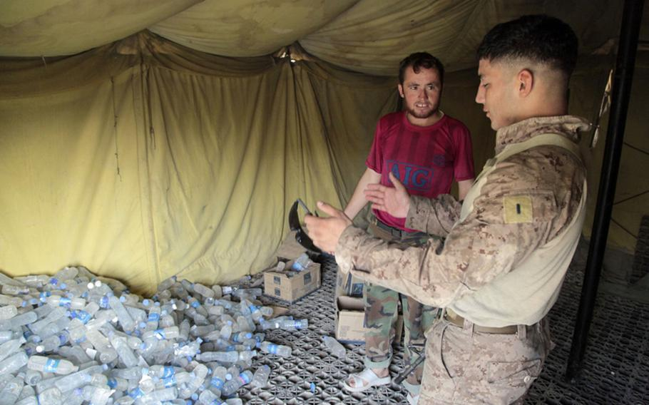 Marine 1st Lt. Mike Cubillos, a 23-year-old Afghan Army adviser from Albany, N.Y., explains to Afghan army Sgt. Amrullah how to better organize his supplies. Amrullah has to call in supply statistics daily to his headquarters, and they deliver water based on the information. He never counts the bottles, but provides estimates to his headquarters.